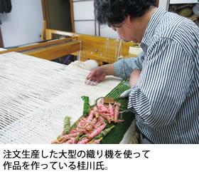 注文生産した大型の織り機を使って作品を作っている桂川氏